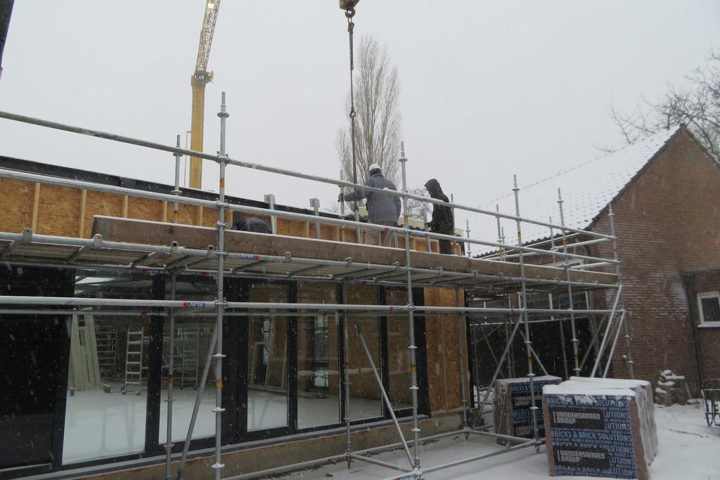 het aanbrengen van de dakplaten gaat, ondanks de sneeuw, gewoon door